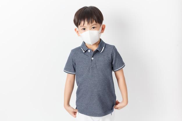 Menino criança asiática vestindo uma máscara de proteção.