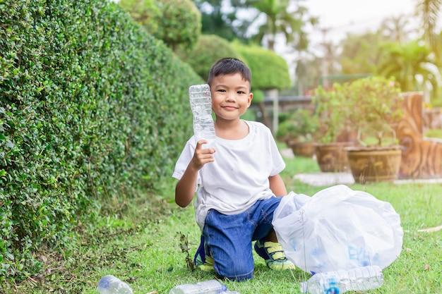 Menino criança asiático é voluntário para limpar o chão do campo.