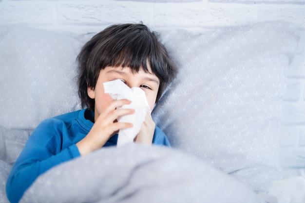 Menino criança assoar o nariz. criança doente com guardanapo na cama. garoto alérgico, temporada de gripe. garoto com rinite fria, resfriado
