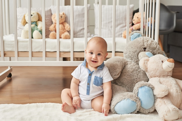 Menino criança brinca brinquedos de madeira em um quarto infantil em cores brilhantes, quarto infantil estilo escandinavo