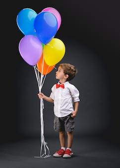 Menino, criança, brincando com balões coloridos (bexigas)
