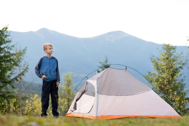 Menino criança caminhante descansando em pé perto de uma barraca de acampamento em um acampamento nas montanhas