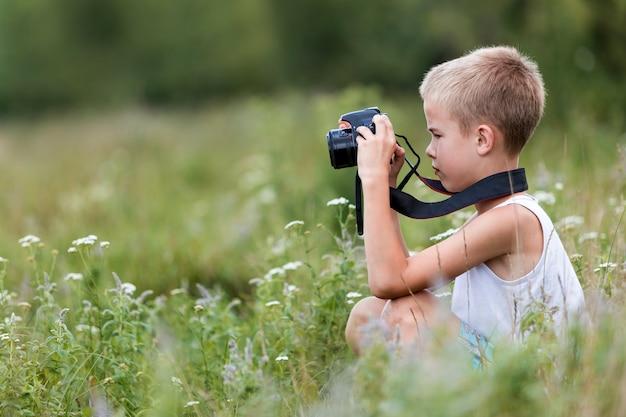 Menino criança com câmera tirando fotos ao ar livre