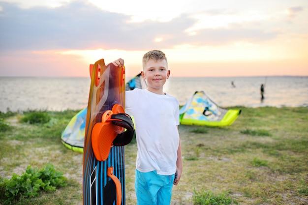 Menino criança, com, um, tábua, para, natação, ou, surfando, sorrindo, ligado, a, mar