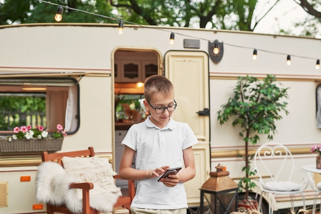 Menino criança com um telefone de férias no verão perto da casa sobre rodas