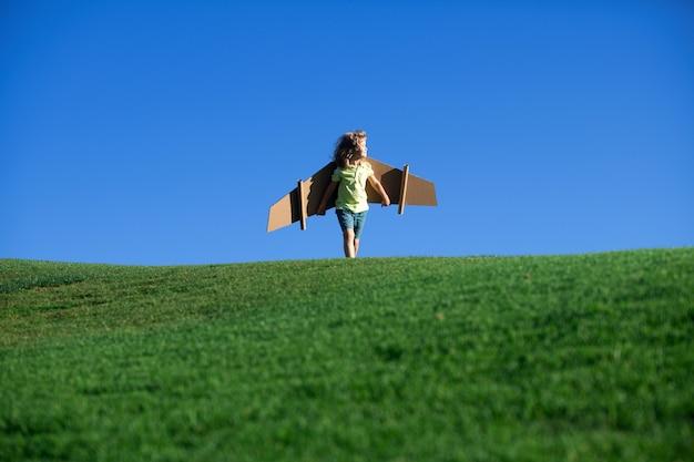 Menino criança como um piloto com asas de brinquedo contra o céu azul.