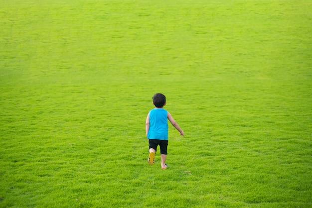 Menino criança correndo para a frente no grande campo de grama verde