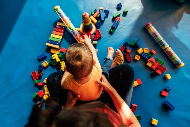 Menino criança e mãe brincando com um brinquedo educacional.