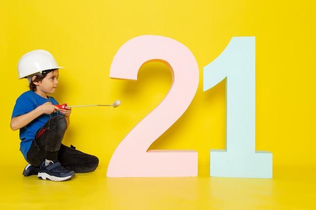 Menino criança em camiseta azul e capacete branco na parede amarela