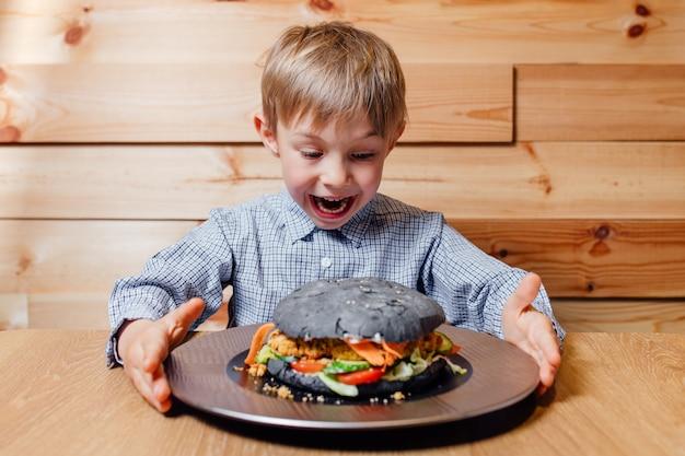 Menino criança espantado com hambúrguer vegetariano preto,