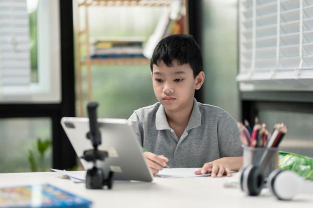 Menino criança está usando se comunica na internet em casa. ensino doméstico, ensino à distância, garotinho asiático fazendo uma aula on-line e feliz pela quarentena do ensino doméstico.
