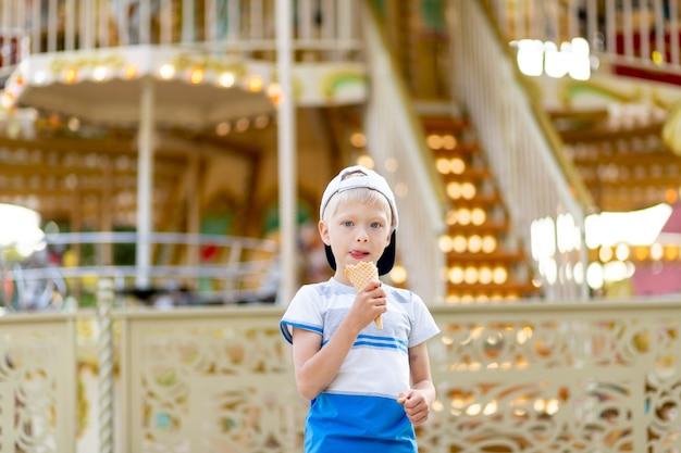 Menino criança feliz andando em um parque de diversões e comendo sorvete