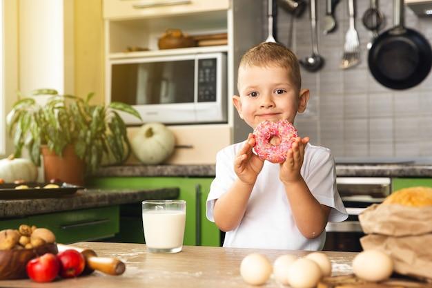 Menino criança feliz bebendo leite e comendo rosquinha na cozinha
