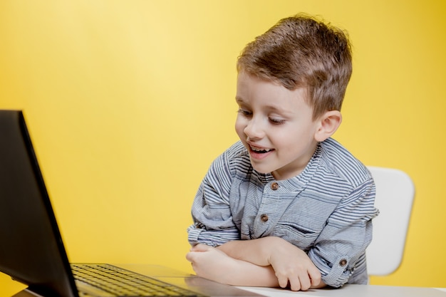 Menino criança feliz sentado à mesa com o laptop e se preparando para a escola