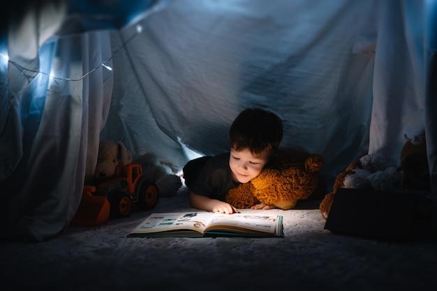 Menino criança lendo com livro e lanterna e ursinho de pelúcia na tenda. antes de ir para a cama