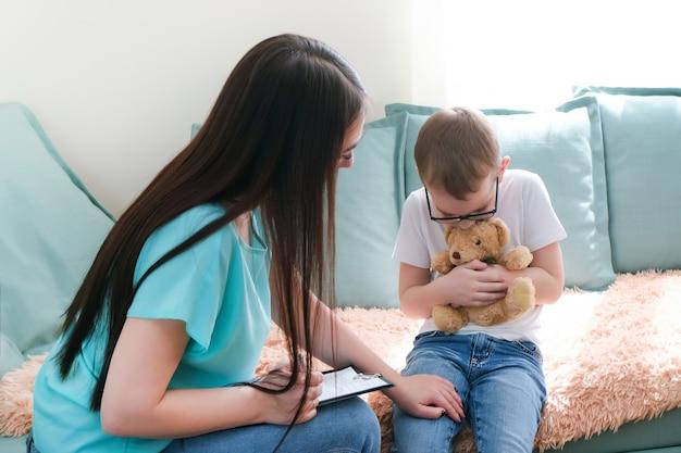 Menino criança no escritório do psicólogo. psicólogo conversando com uma criança, problemas do aluno