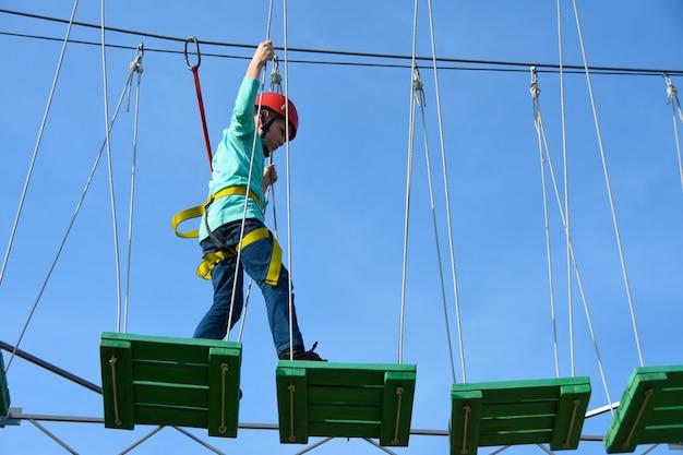 Menino criança, passos, ligado, tábuas madeira, ligado, a, obstáculo, curso, em, um, parque divertimento