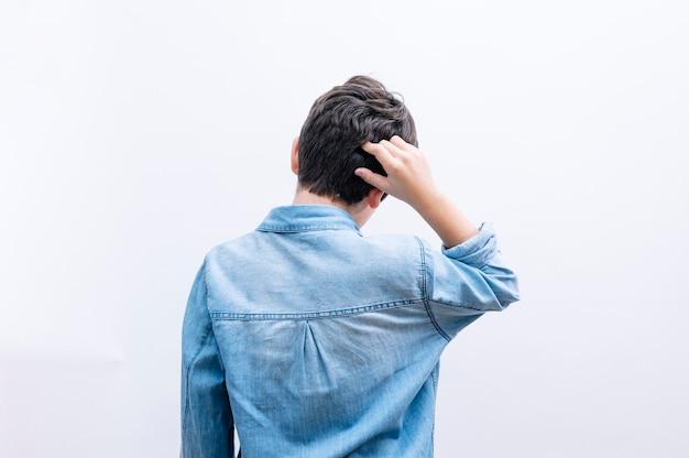 Menino criança pensando em dúvida de costas para a cabeça