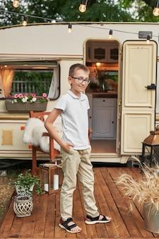 Menino criança perto de uma caravana no verão ao pôr do sol