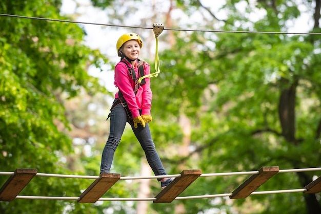 Menino criança se divertindo na aventura parque menino bonito criança aventura escalando fio alto parque despreocupado chi ...