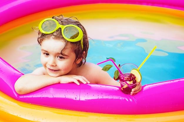 Menino criança se divertindo na piscina. linda criança relaxando na piscina. crianças brincando em
