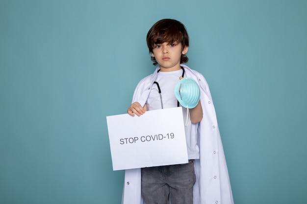 Menino criança segurando parada hashtag covid em terno médico branco e calça jeans cinza na parede azul