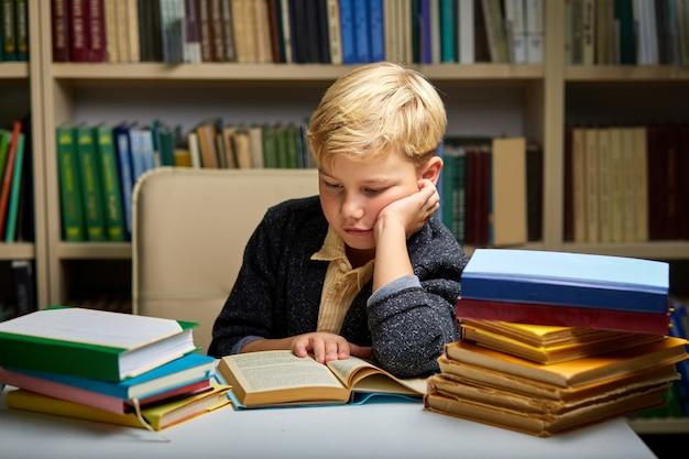 Menino criança sob pressão mental ao ler livros para preparar os exames, na biblioteca.