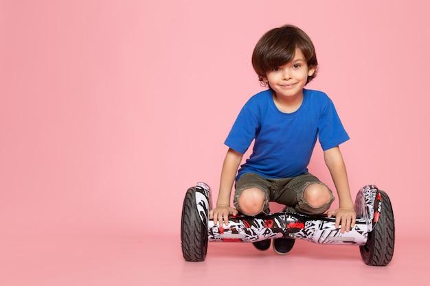 Menino criança sorridente em camiseta azul andando segway na parede rosa