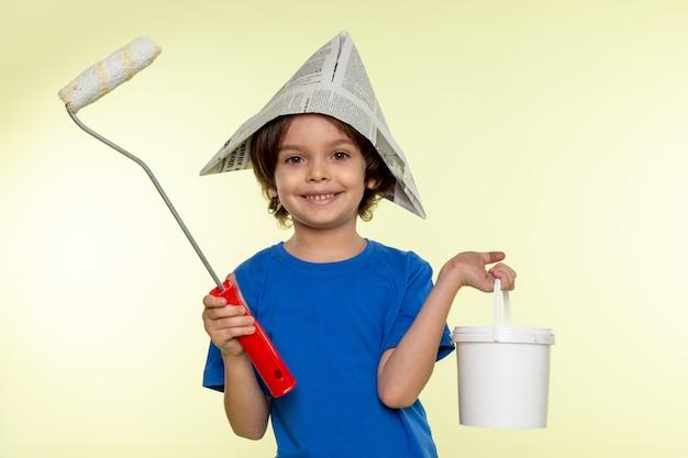 Menino criança sorridente em camiseta azul com pincel e tintas na parede branca