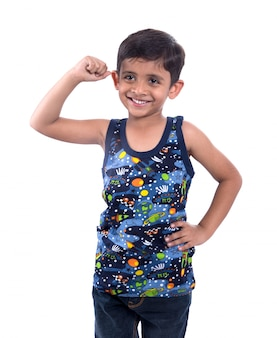 Menino criança sorridente, mostrando sua força de músculos bíceps de mão na parede branca
