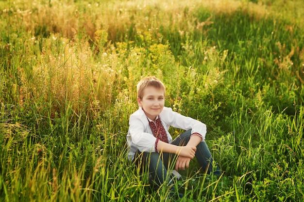 Menino criança ucraniana no bordado no campo