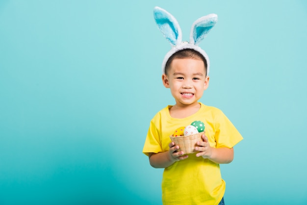 Menino criança usando orelhas de coelho e camiseta amarela, segure a cesta com ovos de páscoa