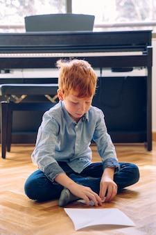 Menino criativo em casa fazendo artes e ofícios. criança pequena de castigo sem escola fazendo atividades educativas em casa