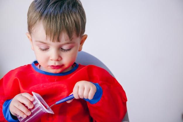 Menino curioso aprendendo a comer. estilo de vida familiar e dieta saudável.