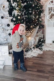 Menino curioso com chapéu de papai noel sorrindo e caminhando perto da árvore de natal