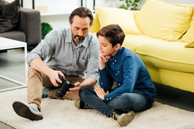 Menino curioso de cabelos escuros sorrindo enquanto está sentado no tapete com seu pai e vendo fotos na tela de sua câmera