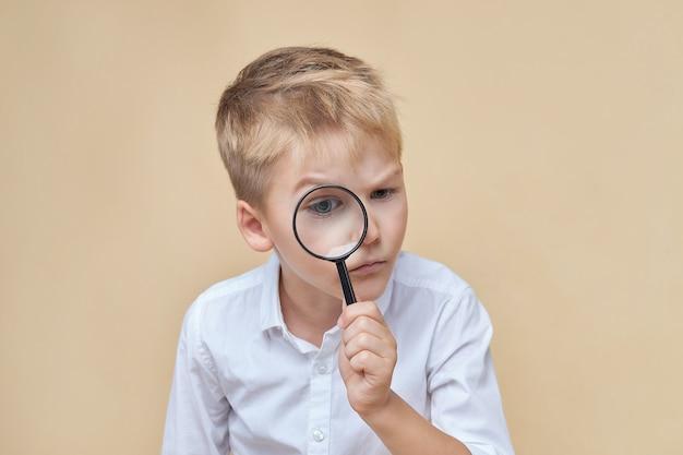 Menino curioso olhando algo embaixo com uma lupa