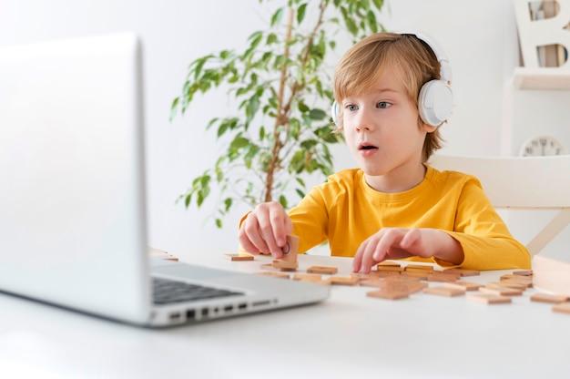 Menino curioso usando laptop e fones de ouvido em casa