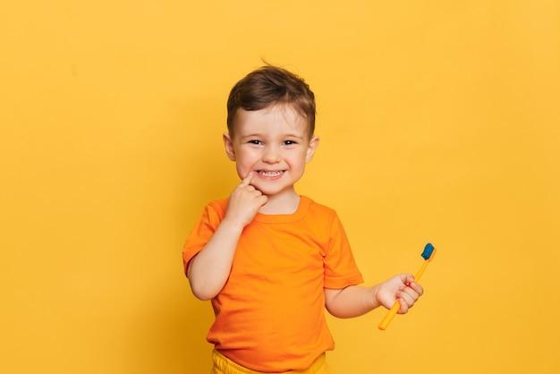 Menino da criança bebê feliz escovando os dentes com uma escova de dentes em uma parede amarela.
