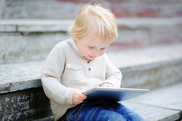 Menino da criança brincando com um tablet digital