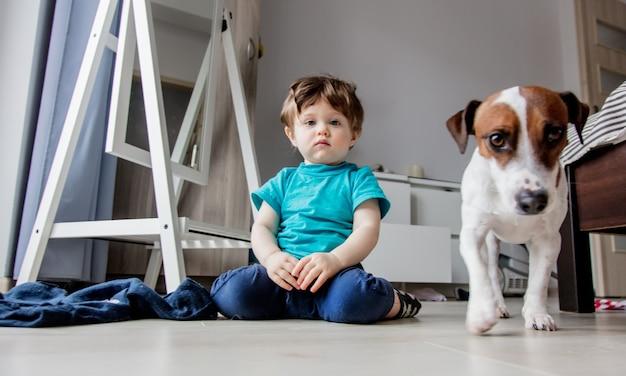 Menino da criança brincar em casa com seu cachorro jack russell terrier.