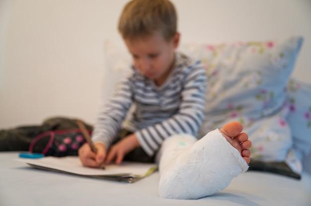 Menino da criança com gesso na perna
