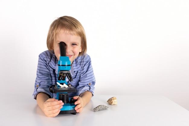 Menino da criança com um microscópio uma lição de vida prática em um fundo branco