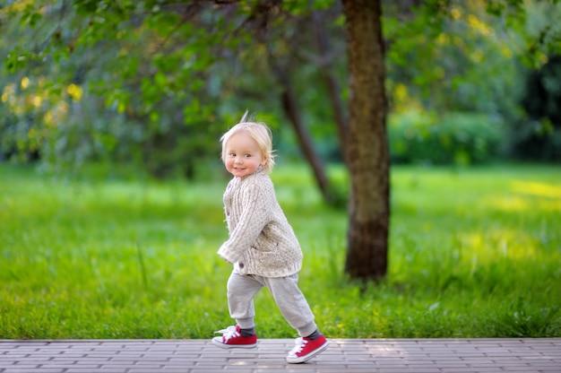 Menino da criança correndo no parque na primavera ou no dia de verão