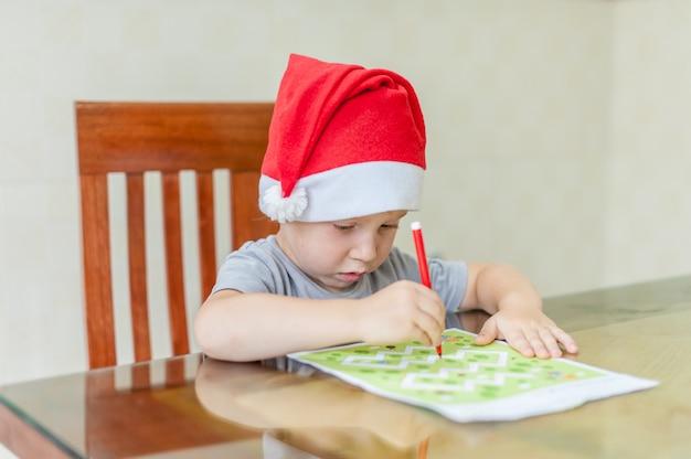 Menino da criança desenha caminho de caneta de feltro no labirinto. conceito de desenvolvimento inicial