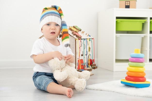 Menino da criança do bebê com chapéu engraçado e camiseta branca, brincando com placa ocupada e ursinho de pelúcia em casa.
