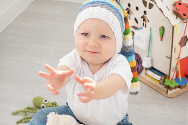 Menino da criança do bebê no chapéu engraçado e camiseta branca, brincando com placa ocupada e ursinho de pelúcia em casa.