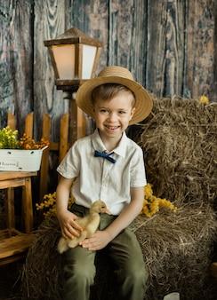 Menino da criança feliz com cabelo castanho e um chapéu de palha está sentado no feno com um patinho. comemorando a páscoa com as crianças
