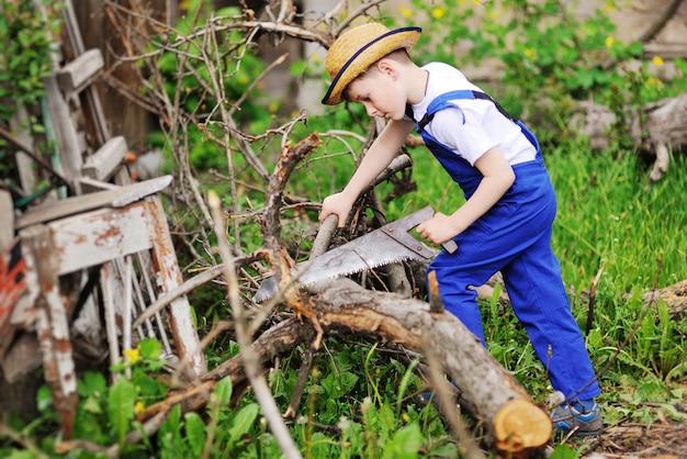 Menino da criança na roupa de trabalho azul e em uma serra de madeira do sawing do chapéu de palha.
