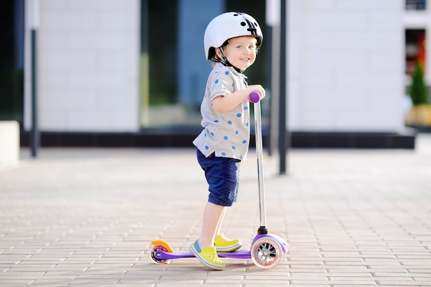 Menino da criança no capacete de segurança, aprendendo a andar de scooter